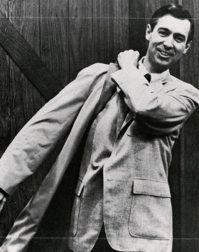 Photo of Fred Rogers putting on his trenchcoat, smiling