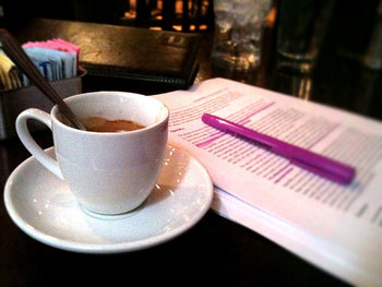 Photo of a coffee cup and on an open book with highlighted pages sitting on a restuarant table