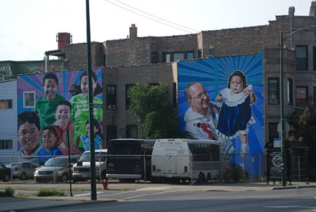 Photo of two murals painted on the side of a building. One mural shows a priest holding a baby and the other shows six children representing diverse cultures.