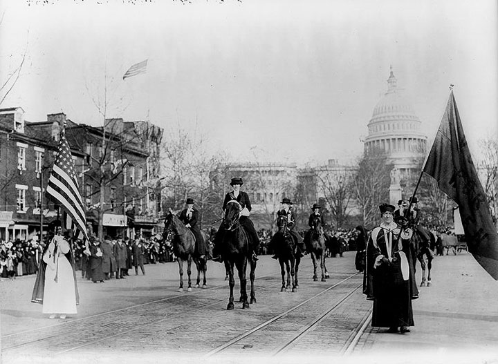 Black and white photograph (author unknown) of a suffragette parade.In the foreground are women dressed in black gowns with regalia. Several are on horses. In the background the US Capitol looms hazily.