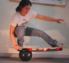 Picture of a girl trying to balance on a bowling bowl using a board specially designed, it would appear, for this purpose.