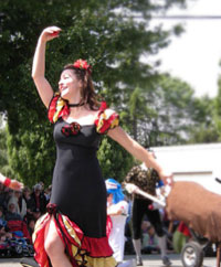 Photo of a woman striking a pose in the costume of flamenco; in the background the accoutrements of a solstice parade.