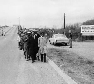 People marching along the side of a road while a police officer looks on.