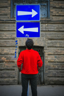 Photo of a boy staring at two traffic signs. An arrow on one sign points left. The arrow on the other side points right.