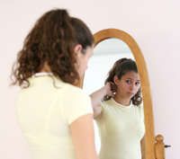 Young girl looking in a mirror.