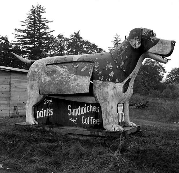 A giant wooden floppy eared dog with its tongue hanging out is advertisement for a refreshment stand in Oregon