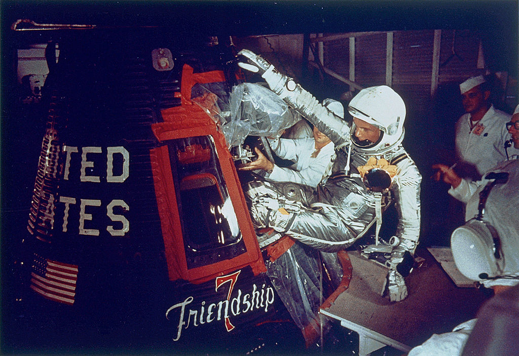 A colored photograph of astronaut John Glenn entering the space capsule, Friendship 7.