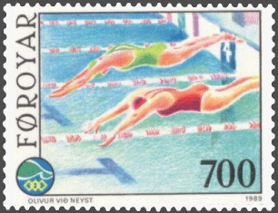 a colorful postage stamp that depicts women diving off the side of the pool at the start of a swimming race