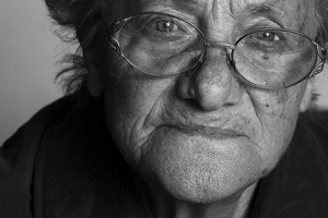 A photograph/portrait of an older woman. She is wearing glasses and looking into the camera.