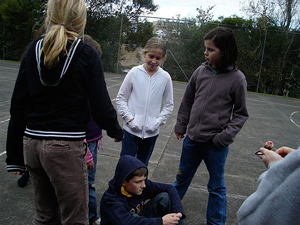A photograph of several young people in a park or school yard. They appear to be planning something.