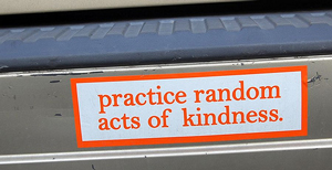 """A photograph of a bumper sticker that reads """"practice random acts of kindness."""""""