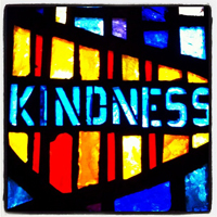 """A photograph of a stained glass window with the word """"kindness"""" in the center of it."""