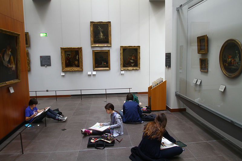 A photograph of several young students at the Louvre Museum. They are sitting and sketching the paintings that are looking at on the walls surrounding them.