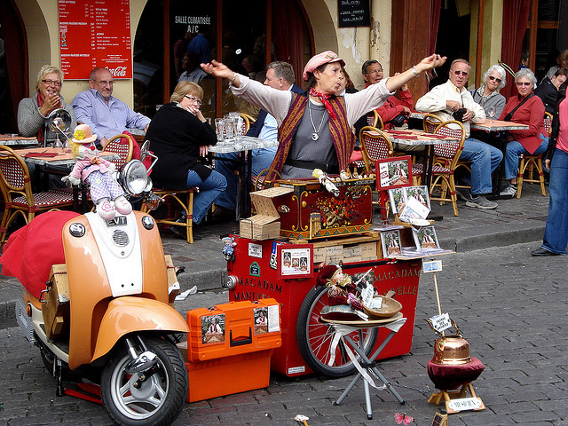 A photograph of a street performer entertaining customers of an outdoor cafe. The performer is surrounded by props.