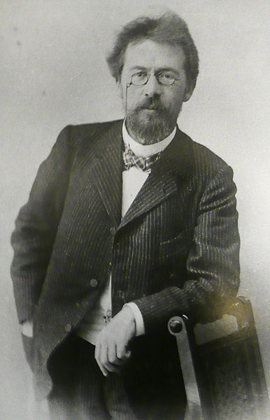 A photograph/portrait of Antonin Chekov. He is a middle aged man with a goatee and glasses. He is wearing a suit and a bow tie.