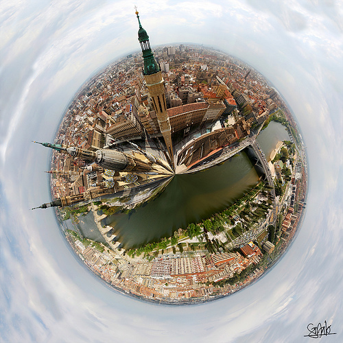 """circle with a city fit into it, buildings jutting up disproportionately as if the city is being squeezed from a tube"""""""