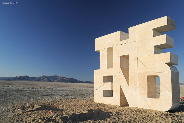 """A photograph of a structure of the words """"the end"""" in a desert"""