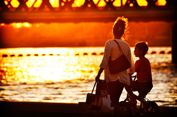 A photograph of a mother and son talking. He is on a bike and she is walking next to him. They are by a river and a bridge.