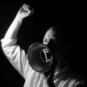 A photograph of a man telling into a megaphone.