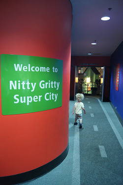 """photo of the entrance to a museum exhibition; a green sign posted on a bright red wall read """"Welcome to Nitty Gritty Super City."""""""