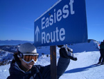 """photo of a young woman in a snowsuit and sun goggles pointing to a sign on a snow-covered mountain that reads """"Easiest Route"""""""