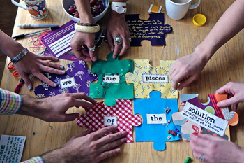 """photo of eight hands piecing together puzzle pieces made of fabric that together read """"we are pieces of the solution"""""""