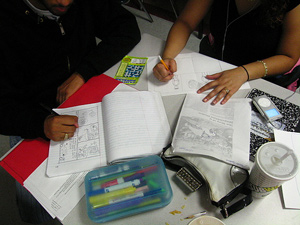 A photograph of two students working together on an assignment. They are both writing.