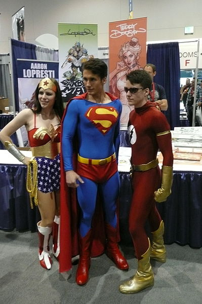 A photograph of two young men and a woman dressed up as the superheroes Wonder Woman, Superman, and the Flash