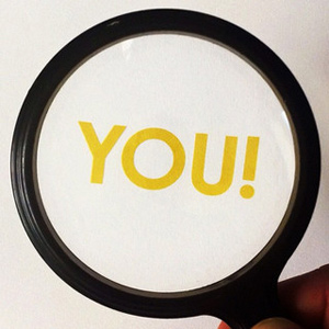 """A photograph of a magnifying glass being held over the word """"You!"""""""
