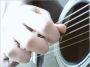 A photograph of a person playing an acoustic guitar. Visible is the picking hand over the sound hole and the strings.