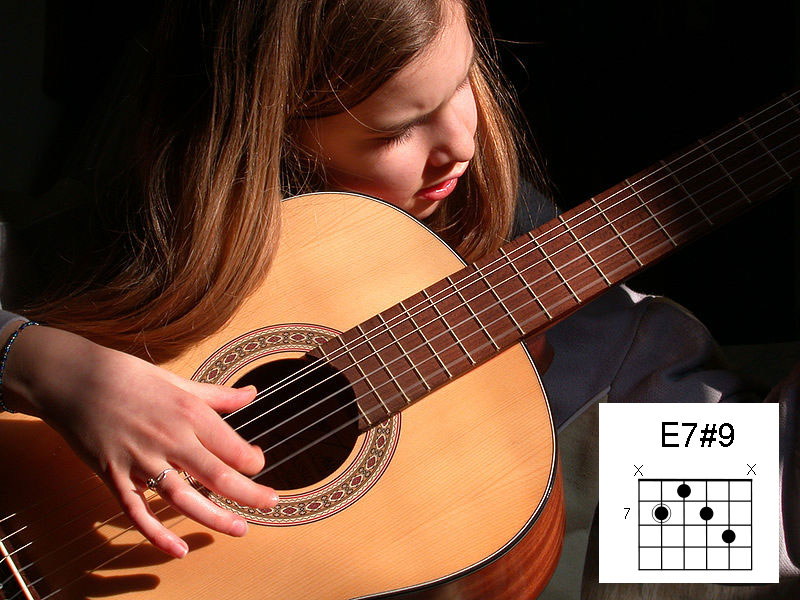 A photograph of a young girl playing an acoustic guitar