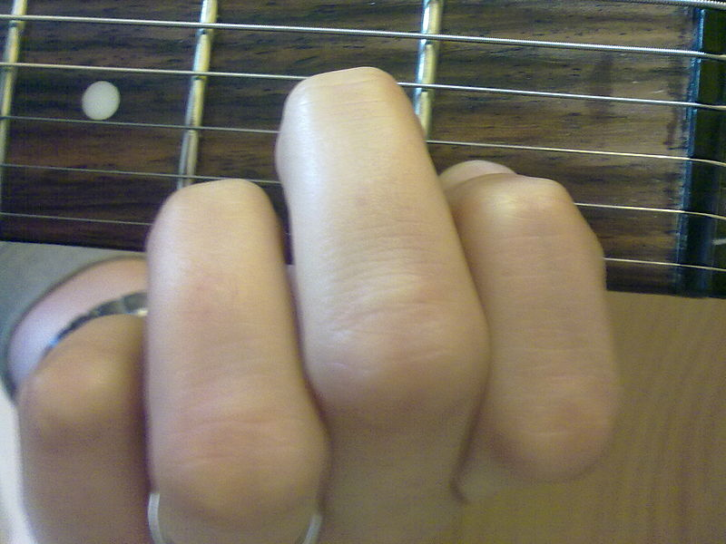 A photograph of a person's fingers on a guitar fret playing a chord