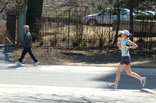A photograph of a man walking and a woman running along a trail